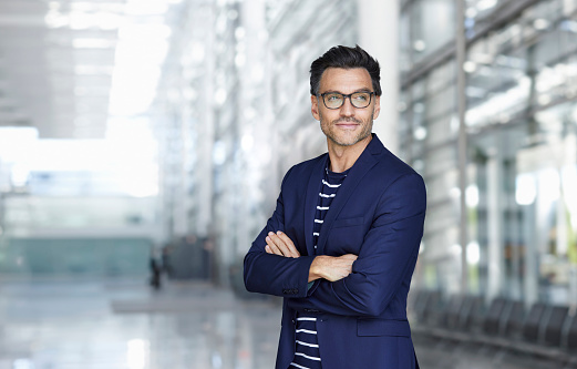 Portrait of stylish businessman with stubble wearing blue suit and glasses - gettyimageskorea