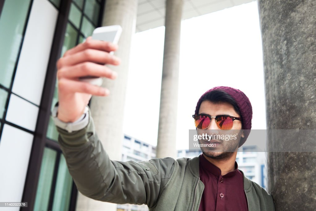 Portrait of stylish man with sunglasses and purple hat taking selfie via mobile phone : Stock Photo