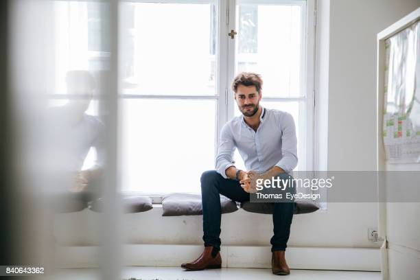Portrait Of Stylish Office Manager Sitting By Window