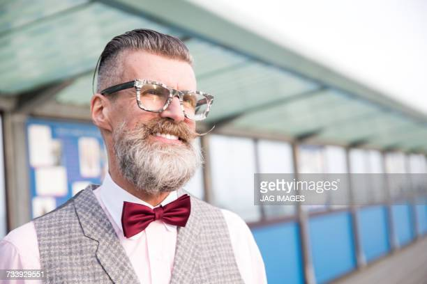 Portrait of stylish senior man with eyeglasses and handlebar moustache on pier