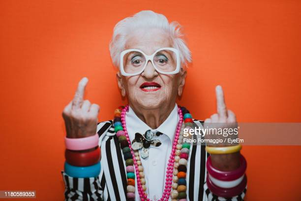 portrait of stylish senior woman wearing colorful jewelry showing middle finger against red background - negative emotion stock pictures, royalty-free photos & images