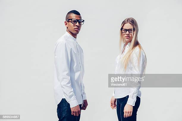 portrait of stylish young couple wearing matching clothes in front of white background - couple mixte noir blanc photos et images de collection