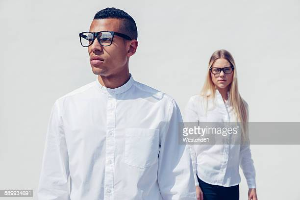 portrait of stylish young couple wearing matching clothes in front of white background - einfachheit stock-fotos und bilder