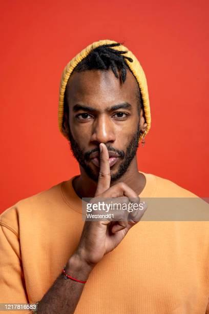 portrait of stylish young man shushing in front of orange wall - na moda descrição imagens e fotografias de stock