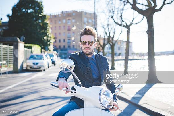 Portrait of stylish young man sitting on moped at roadside