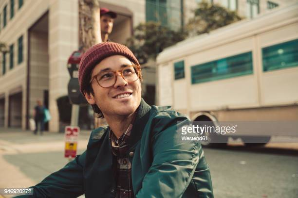Portrait of stylish young man sitting on sidewalk