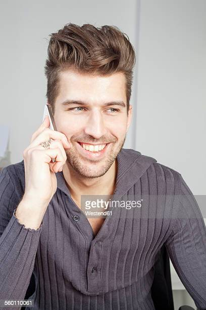 portrait of stylish young man telephoning in an office - ポンパドール ストックフォトと画像