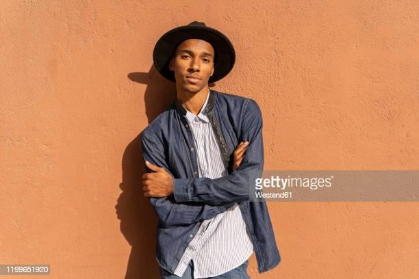 portrait of stylish young man wearing a hat at a wall - cadrage à la taille photos et images de collection