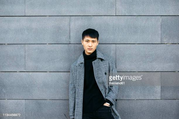 portrait of stylish young man wearing black turtleneck pullover and grey coat - gray coat stock pictures, royalty-free photos & images