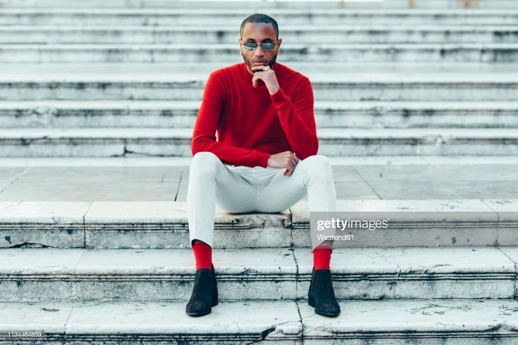 Portrait of stylish young man wearing red pullover and socks sitting on stairs : ストックフォト