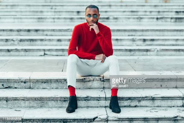 portrait of stylish young man wearing red pullover and socks sitting on stairs - men fashion stock pictures, royalty-free photos & images