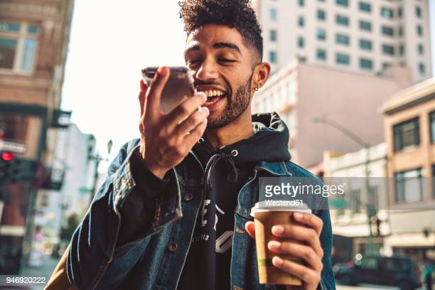 portrait of stylish young man with coffee and smartphone on the street - 発話 ストックフォトと画像