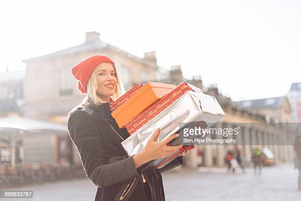 Portrait of stylish young woman carrying stack of christmas gifts, Covent Garden, London, UK