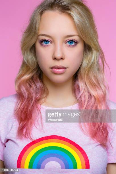 Portrait of stylish young woman in front of pink background