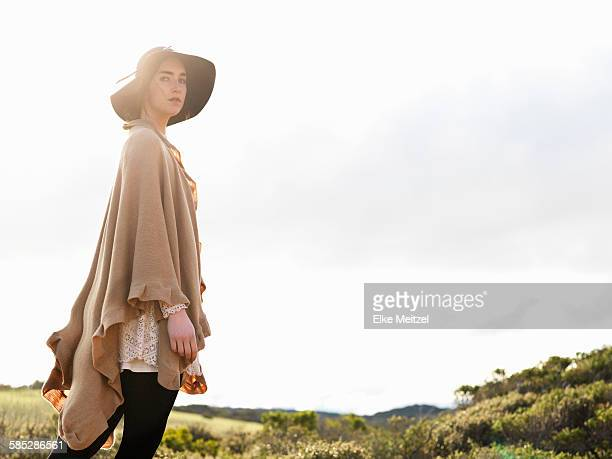 Portrait of stylish young woman wearing felt hat and shawl, Point Addis, Anglesea, Victoria, Australia