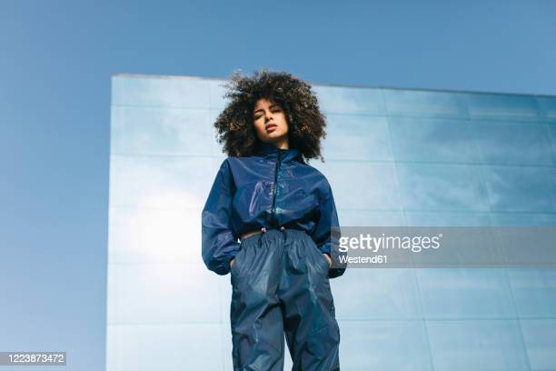 portrait of stylish young woman wearing tracksuit outdoors - roupa desportiva imagens e fotografias de stock