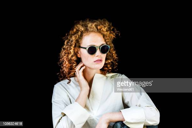 portrait of stylish young woman with curly red hair wearing sunglasses in front of black background - óculos escuros acessório ocular - fotografias e filmes do acervo