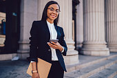 Portrait of successful African American businesswoman dressed in stylish suit holding in hand folder and mobile phone while standing outdoors near financial office, young woman lawyer using smartphone