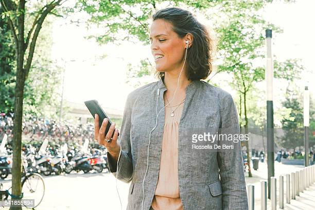 Portrait Of Successful Businesswoman Using Smartphone In Urban Landscape