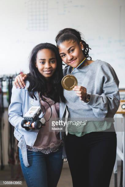 portrait of successful female students holding robot and gold medal while standing in classroom at high school - teen awards foto e immagini stock