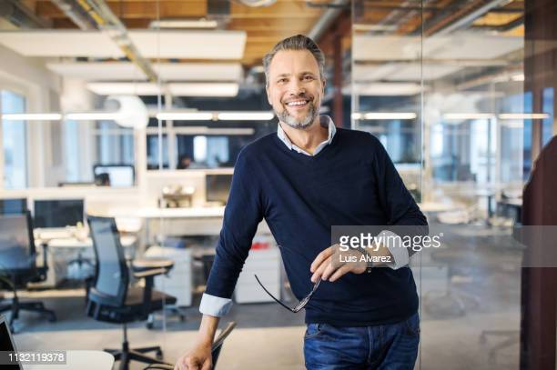 portrait of successful mid adult businessman - geschäftsmann stock-fotos und bilder