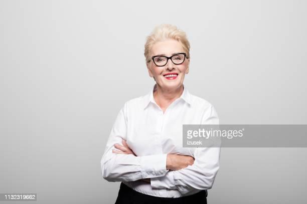 porträt erfolgreicher senioren-unternehmer lächelnd - arme verschränkt stock-fotos und bilder