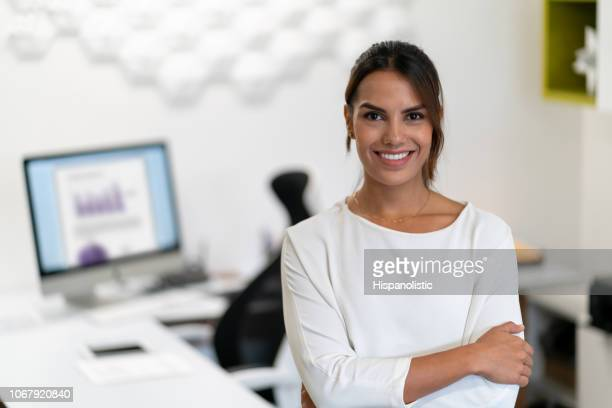 Portrait of successful young businesswoman looking at camera smiling with arms crossed at the office