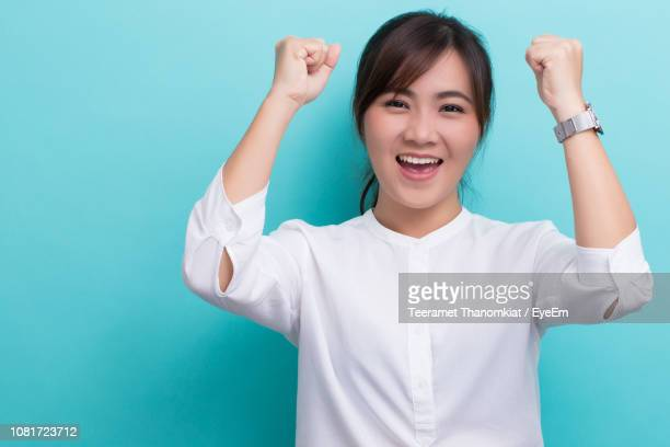 portrait of successful young woman clenching fists against blue background - blouse stock pictures, royalty-free photos & images