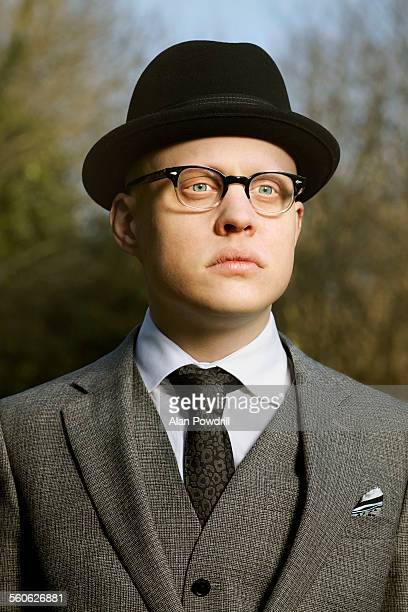 Portrait of suited man in glasses and hat