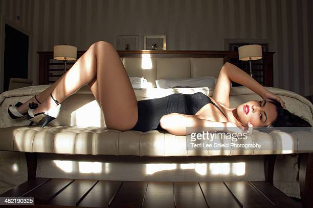 Portrait of sultry young woman lying on bedroom seat