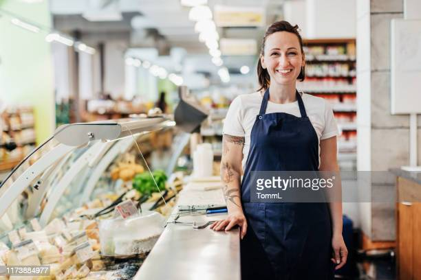 portrait of supermarket clerk standing at counter - delicatessen stock pictures, royalty-free photos & images