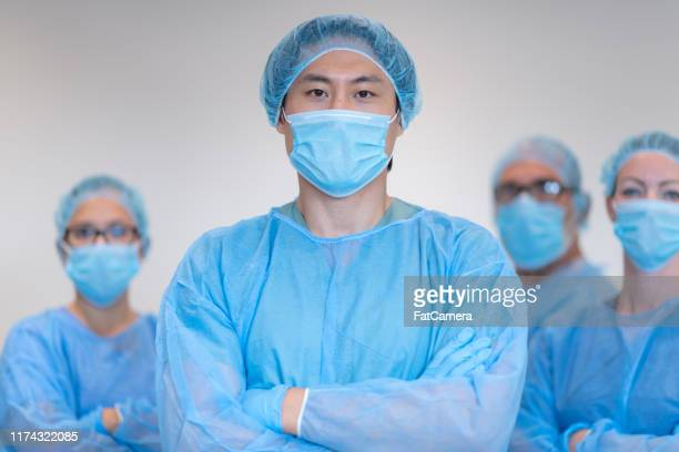 portrait of surgical team - operating gown stock pictures, royalty-free photos & images