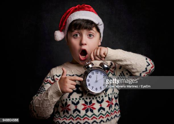 portrait of surprised boy gesturing at alarm clock against black background - countdown stock pictures, royalty-free photos & images