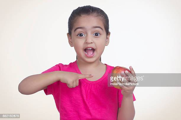 Portrait of surprised girl showing apple against colored background