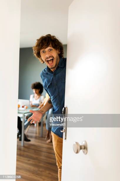portrait of surprised man with friends in background opening the door - 30 39 años fotografías e imágenes de stock