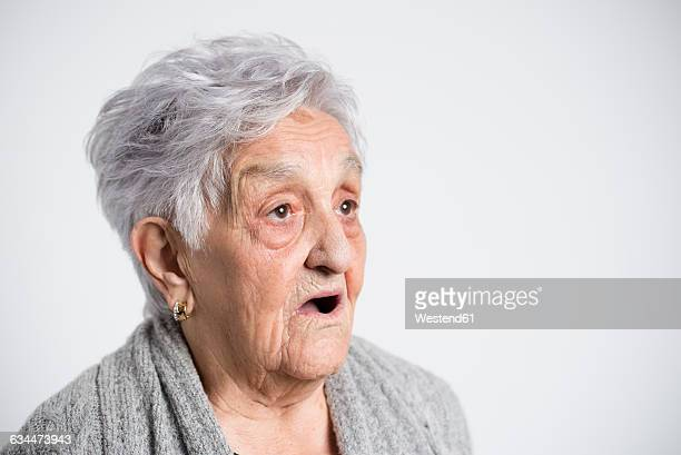 Portrait of surprised senior woman in front of white background