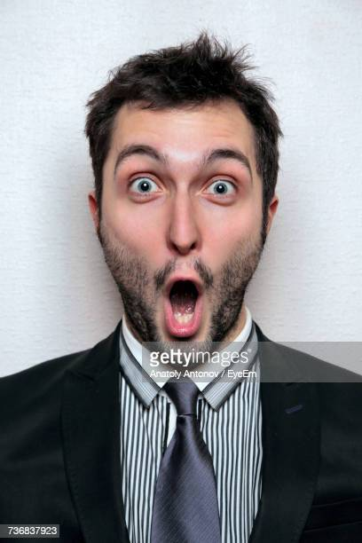Portrait Of Surprised Young Businessman Pointing Against Wall