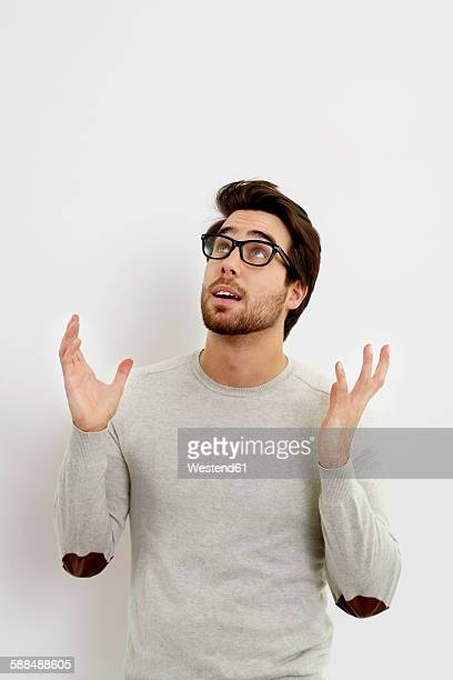 Portrait of surprised young man looking up in front of white background