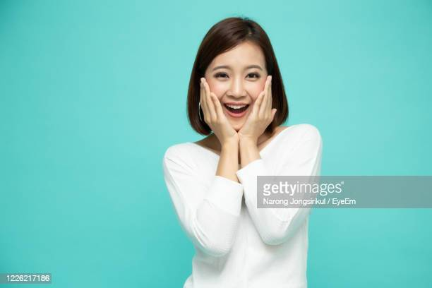 portrait of surprised young woman against blue background - cheek stock pictures, royalty-free photos & images