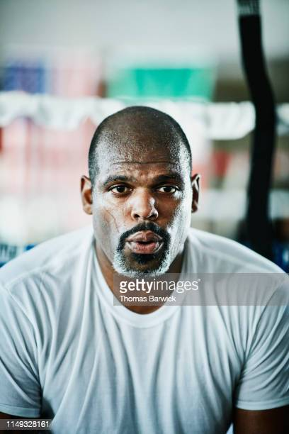 portrait of sweating male boxer breathing heavily after workout in boxing gym - facial expression stock pictures, royalty-free photos & images