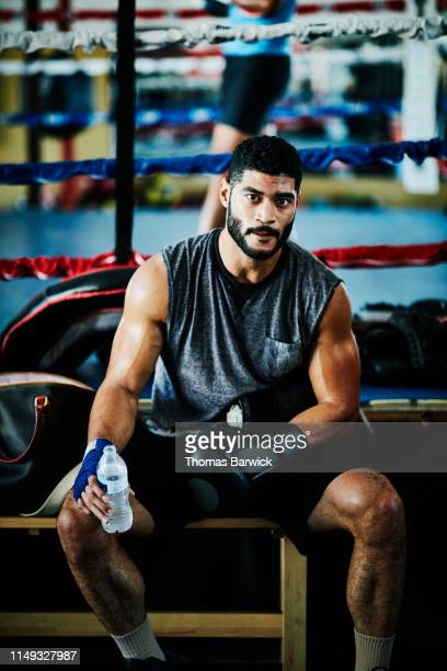 portrait of sweating male boxer resting during training session in boxing gym - boxing shorts stock pictures, royalty-free photos & images