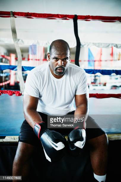 portrait of sweating male boxer sitting on edge of ring during training session - boxing shorts stock pictures, royalty-free photos & images