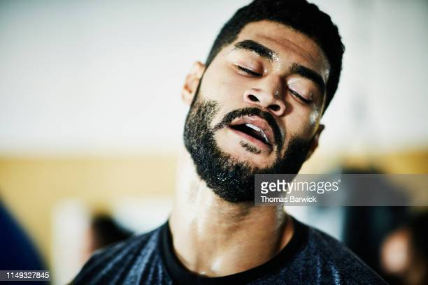 portrait of sweating male boxer with eyes closed training in boxing gym - exhaustion stock pictures, royalty-free photos & images