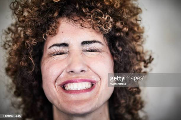 portrait of sweating woman with curly hair - anstrengung stock-fotos und bilder