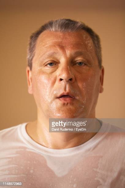 portrait of sweaty man on beige background - one man only stock pictures, royalty-free photos & images
