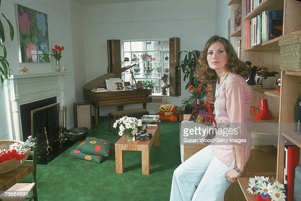 Portrait of Swedish actress Maud Adams as she leans against a bookself in her living room April 1975