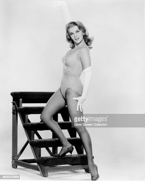 Portrait of SwedishAmerican actress AnnMargret in elbow gloves a onepiece swimsuit and heels as she poses with one foot on a shirt portable staircase...