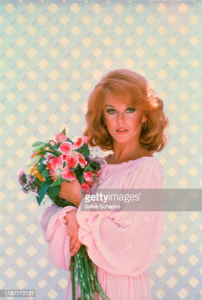 Portrait of Swedishborn American actress AnnMargret a bouquet of flowers in her arms as she poses against a pale blue trellis Los Angeles California...