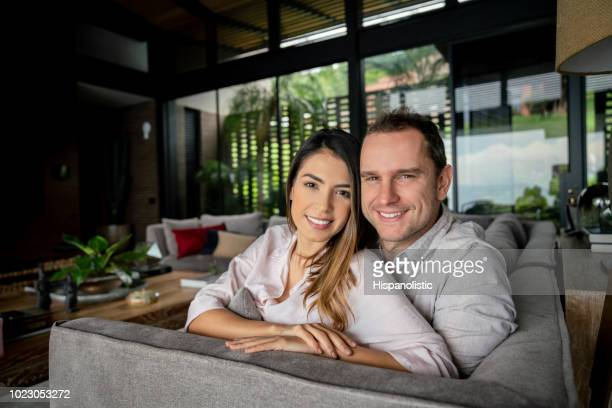 Portrait of sweet couple at home sitting on the couch embracing each other looking at camera very happy
