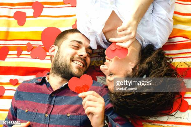 Portrait of sweet cute couple lying head to head on the floor with small red hearts around
